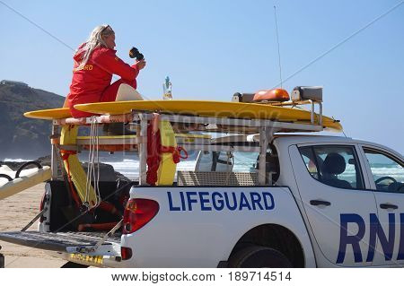 Newquay, Cornwall, Uk - April 7 2017: Female Rnli Lifeguard Keeping Watch On Top Of A Truck On A Sur