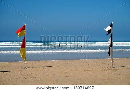 Newquay, Cornwall, Uk - April 7 2017: Red, Yellow,black And White Beach Lifeguard Flags Blowing In T