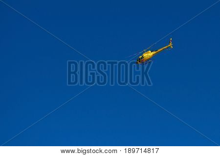 SAINT MORITZ, SWITZERLAND, AUG,17, 2010: Yellow red touristic passenger helicopter flying in blue sky no clouds. Yellow chopper copter Sunny summer day Helicopter sightseeing tours. Helicopter air one