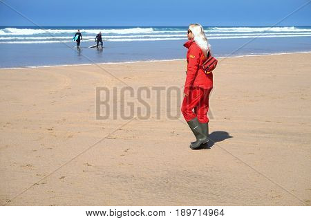 Newquay, Cornwall, Uk - April 7 2017: Female Rnli Lifeguard Keeping Watch On A Surfing Beach In Newq