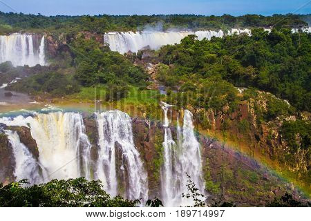 Multistage system of waterfalls creates rainbow. Iguazu Falls National Park - grandiose complex of waterfalls on the border of Argentina, Brazil and Paraguay