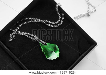 Large emerald pendant on a chain in black jewel box