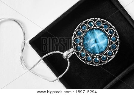 Turquoise and topaz medallion in black jewel box closeup