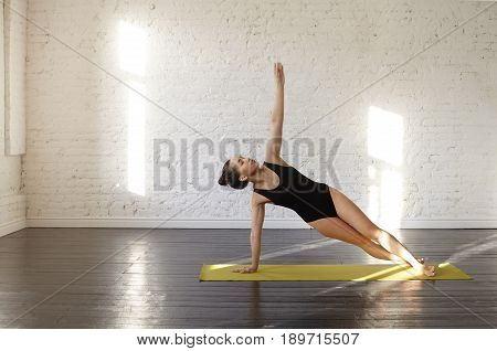 Beautiful asian female practicing yoga asana Vasisthasana in the bright sunny morning room. Pretty girl standing in Side Plank Pose. Calmness and relax, woman happiness. Yoga and health concept
