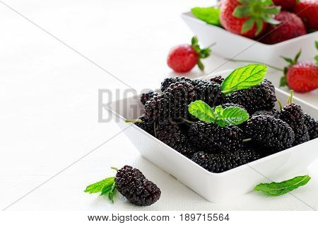 Fresh ripe mulberries and strawberries with mint in bowl on white background, copy space. Horizontal