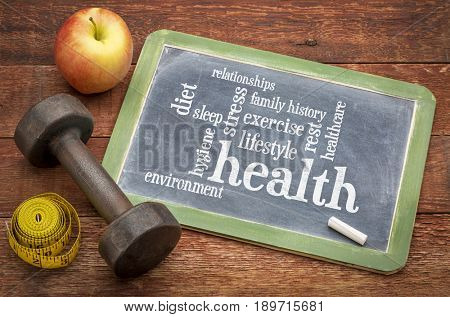 health concept - word cloud of contributing factors (diet, lifestyle, healtcare, family history, environment, exercise, stress, relationships, sleep, rest, hygiene), white chalk text on a blackboard