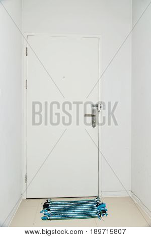 Colorful asian floor mat near white door. Vertical shot of an closed wooden front door without windows