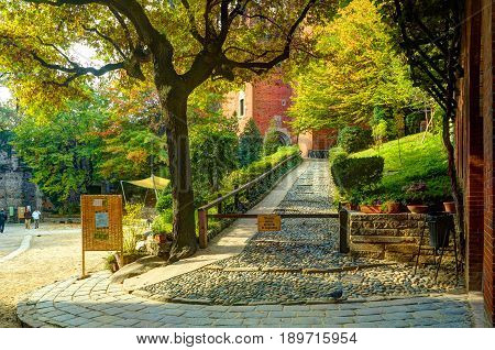 TURIN, ITALY, OCT, 20, 2007: Evening view on green trees antique castle patio Borgo Medioevale city garden park. Highlighting sun. Italy Italian architecture ornaments. Italy holidays vacations tours