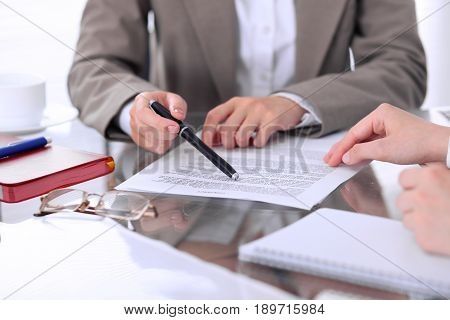 Group of business people and lawyers discussing contract papers sitting at the table, close-up