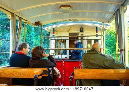 TURIN, ITALY, OCT, 21, 2007: Tourists passengers in retro train saloon of Italian mountain electric old fashion train to Superga church. Inside passenger coache. Italy holidays vacations tours