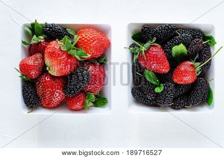 Fresh ripe mulberries and strawberries with mint in bowl on white background, copy space. Horizontal, top view