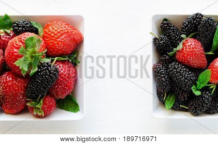 Fresh ripe mulberries and strawberries with mint in bowl on white background, copy space. Horizontal banner, top view