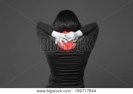 Neck pain woman with backache on gray background with red dots