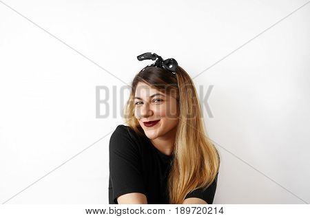 Funny woman on white background. Portrait of woman smiling with pretty sly smile. Cheerful female model joyful. Positive human emotion facial expression body language