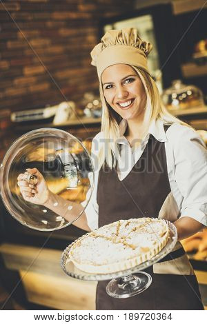 Bakery Female Worker Posing With Apple Tart In Baker Shop