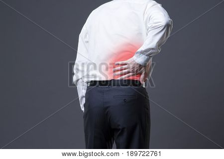 Back pain kidney inflammation ache in man's body on gray background with red dot