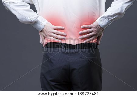 Back pain kidney inflammation ache in man's body close-up on gray background with red dot
