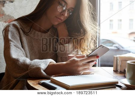 Beautiful European female student using cell phone sitting at a window in a cafe checking newsfeed on her social network accounts. Pretty girl surfing internet on mobile focus on phone