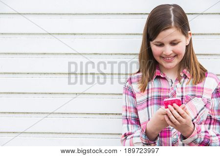 Pre Teen Girl Texting On Mobile Phone In Urban Setting