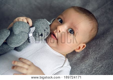 newborn to three months lying in bed and hugs the rabbit toy