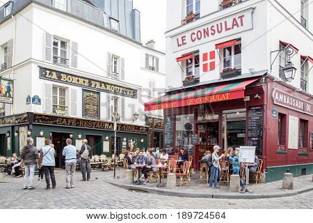 Paris, France - May 12, 2017: The streets of Montmartre district with people sitting in cafes and restaurant