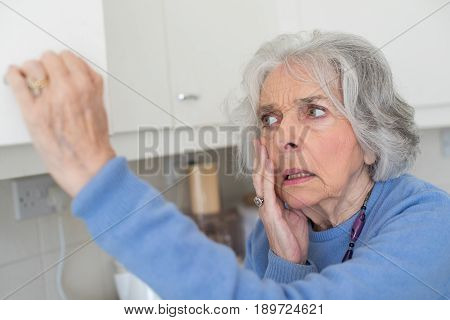 Forgetful Senior Woman With Dementia Looking In Cupboard