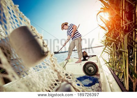 Old fisherman taking out the fishing net
