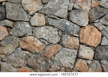 An old brown and grey colors stone wall background.