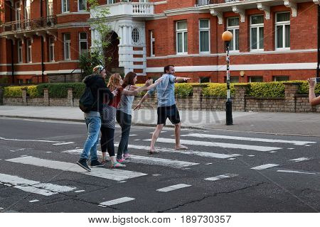 LONDON, GREAT BRITAIN - MAY 17, 2014: Four unidentified young people cross Abbey Road on the famous crossing on which the most famous photo of the Beatles was made.