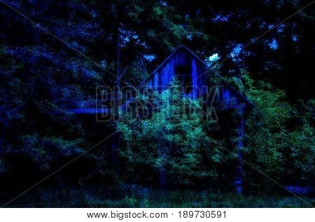A terrible and mysterious abandoned wooden house at night in the country all overgrown with trees