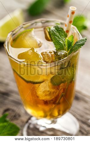 Tasty fresh refreshing summer tea drink with ice cold tea lime and mint in glass on wooden background. Closeup.