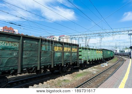 SARATOV RUSSIA - MAY 6 2017: Freight train at the railway station. Old rusty metal cars are painted with green paint.
