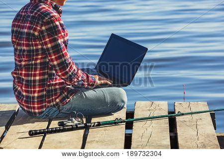 A fisherman man works on a laptop sits on a wooden pier near the lake next to it there is a fishing pole.