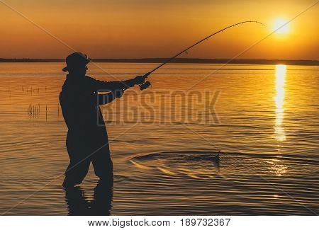 The fisherman catches fish for spinning and stands in the water against a beautiful sunset.