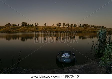 Moored fishing inflatable rubber boat near the shore of the lake of night. Night fishing. Dinghy with oars.