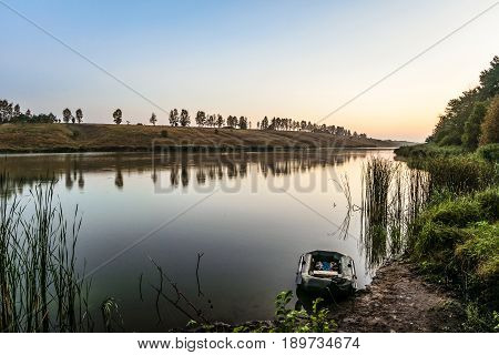 Moored fishing inflatable rubber boat and a fishing rod near the shore of the lake. Summer early morning and sunrise. Dinghy with oars.