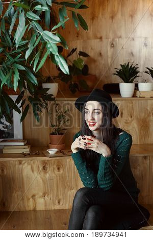 Vertical portrait of smiling stylish female student in trendy black hat with tea cup in her hands looking away sitting on wooden background with plants in university cafe. The break between lectures