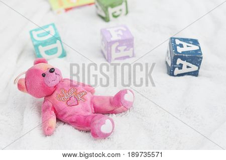 A cute pink bear soft toy with I Love You words written on the bear.  Cubes of alphabet around the soft toy.  White background.