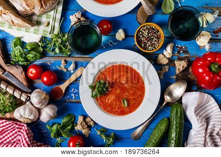 Tasty appetizing classic spanish soup gazpacho in white plates on rustic blue table with bread garlic and spices. Dinner Food Concept. Top View. Copy Space.