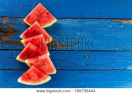 Sliced watermelon Top View. Many slices on an old rustic blue table. Side composition with copy space. Food Backrgound.