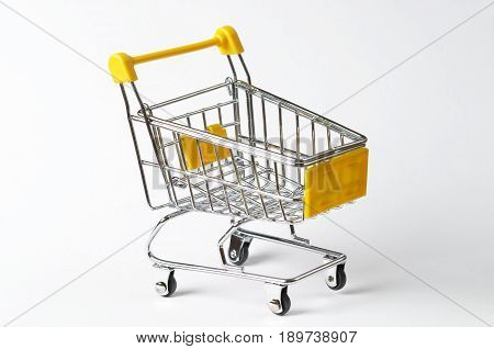 Metallic yellow shopping trolley over white background