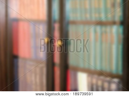 Books behind glass in a bookcase. Blurred horizontal background. Close-up.