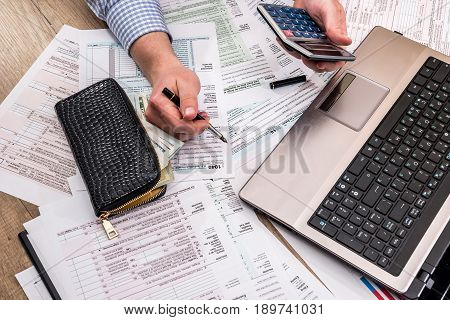 Businessman  Filling 1040 Tax Form With Help Laptop At Office Desk