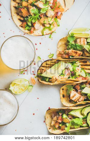 Healthy corn tortillas with grilled chicken fillet, avocado, fresh salsa, limes, beer over light grey marble background, top view. Healthy food, gluten-free, weight loss, allergy-friendly concept