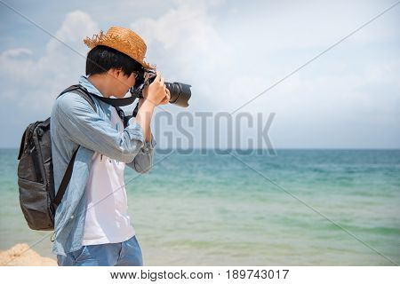 young Asian man photographer with jean shirt and hat take photo of tropical island beach and turquoise sea seascape background for summer holiday and vacation travel concepts