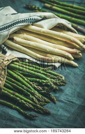 Fresh green and white asparagus in towel over dark grey linen table cloth background, selective focus
