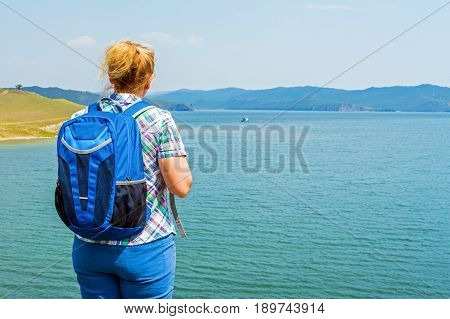 Woman backpacker on the shore of Lake Baikal. Olkhon Gates Strait. In the distance - Olkhon island