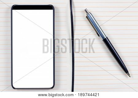 Notepad with elegant pen and bezel less smartphone with blank screen. Ready for mobile application mockup.