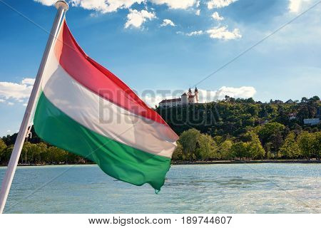 Tihany Abbey viewed from a ship with the Hungarian flag in the front at Lake Balaton Hungary