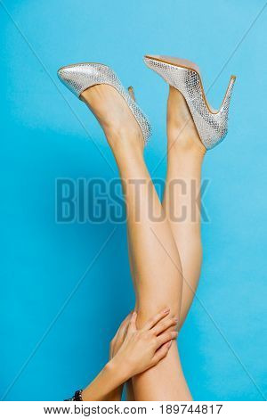 Female fashion. Silver high heels spiked fashionable shoes on sexy long legs. Studio shot against blue